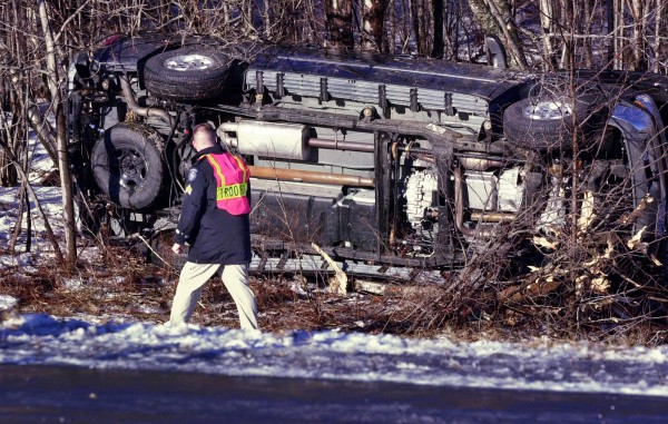 A state official examines the overturned vehicle that Gov. John Baldacci was injured in while traveling southbound on I-295 in Bowdoinham, Maine, on Feb. 4, 2004. Officials insisted March 1, 2004, that the governor was wearing a seat belt when the crash occurred even though computer data captured from the demolished SUV indicate he wasn't buckled up. The governor suffered a mild concussion and broken rib during the accident.