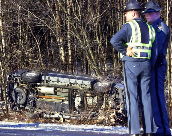 State troopers look over the scene of the accident where the sport utility vehicle in which Gov. Baldacci was riding went off the road and rolled over in Bowdoinham in 2004.