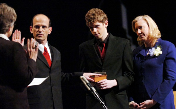 Gov. John Baldacci takes the oath of office to begin his second four-year term as Maine's chief executive as his son, Jack, holds the bible and his wife, Karen, watches Wednesday night at the Augusta Civic Center. Administering the oath of office is Senate President Beth Edmonds (left), D-Freeport.