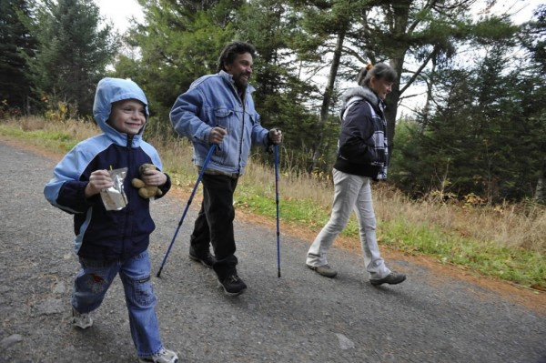 With the help of his walking sticks, Hector Valcarcel, center, of Bangor hikes with his partner Debbie Ritchie, right, and their grandson, Brady Gilreath, in Rolland F. Perry City Forest Saturday afternoon, Oct. 30, 2010. &quotThe things we can't do, I try not to focus on that too much,&quot said Valcarcel whose diagnosis of multiple myeloma and resulting surgeries and chemotherapy has left him struggling to afford health care. (Bangor Daily News/John Clarke Russ)