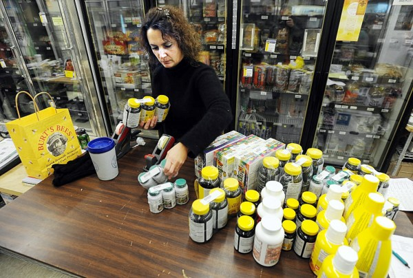 Herbal and supplement sales as-sociate Lisa Wilson unpacks boxes of natural supplements at The Natural Living Center in Bangor on Friday. Herbal supplements are one of many gifts that lend to healthful living this season.