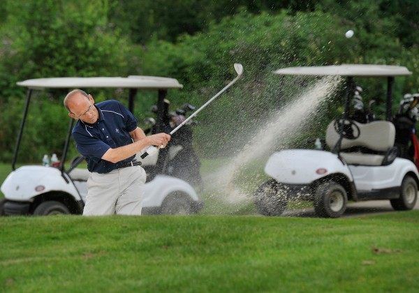 John Baldacci, Bangor, Maine, drives out of a bunker on the 18th hole at Bangor Muni in July 2009.