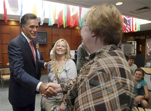In this April 7, 2010 file photo, Sheri Jensen, center watches as former Massachusetts Gov. Mitt Romney shakes hands with her friend Virginia Burke as he arrives at St. Anselm College in Manchester, N.H. (AP Photo/Jim Cole, File)