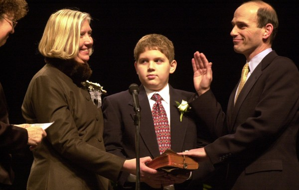 Karen Baldacci and son Jack hold the Bible while Senate President Beverly Daggett swears in John Elias Baldacci as Maine's newest governor at the Augusta Civic Center in 2003.