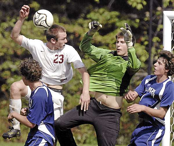 Bangor's Phil Frost (23) tries to get a header on net as Hampden Academy goalkeeper Logan Poirier, Gabe Yamartino and Lukas Kurz defend during a game in September. Frost was named Maine's 2010 NSCAA All-American during the Maine Soccer Coaches Association awards banquet Sunday in Bangor. (BDN File Photo)