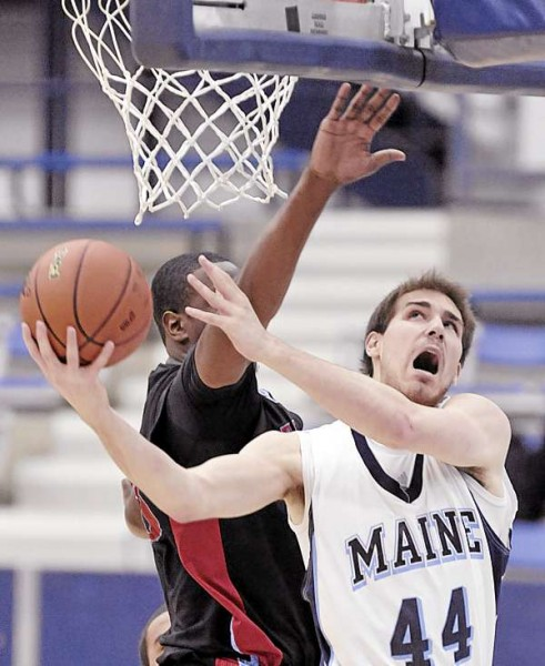 Maine's Mike Allison tries to get a shot off past the arm of Delaware State's James Marcellus in the first half of Monday's men's basketball game in Orono. Delaware State won 75-56.