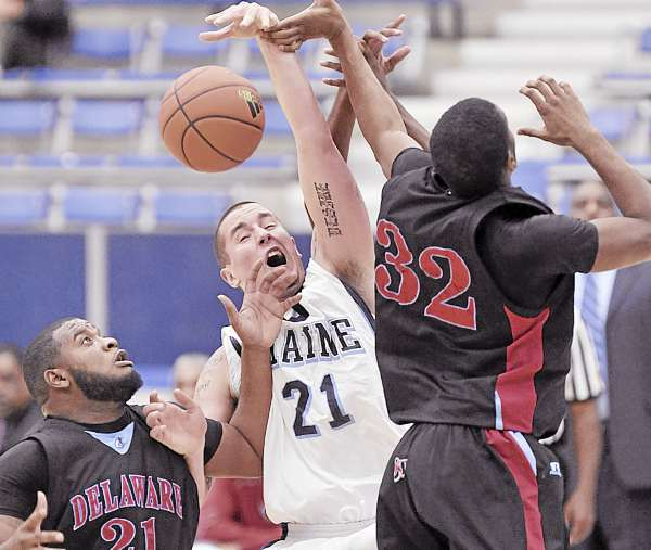 Maine's Sean McNally (21) battles with Delaware State's Marques Oliver (32) and Terron Stowe for control of the ball in the first half of their game Monday at Alfond Arena in Orono. Delaware State won 75-56.