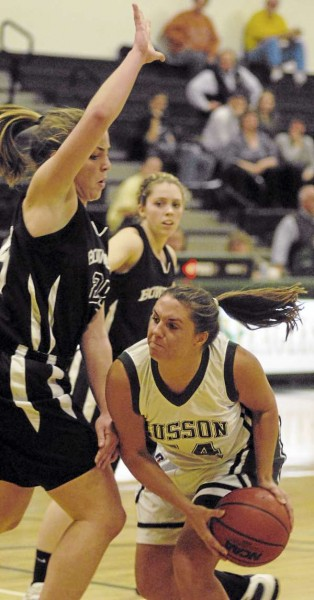 Bowdoin's Alexa Barry defends as Husson's Stephanie Comstock ducks under before going up for a shot in first-half action of Tuesday night's game at Newman Gym in Bangor. Bowdoin's Kaitlin Donahoe looks on. Bowdoin won 89-55. (BDN Photo by Linda Coan O'Kresik)
