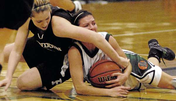 Bowdoin's Kaitlin Donahoe and Husson's Amanda Gifford scramble for a loose ball in first-half action of Tuesday night's game at Newman Gym in Bangor. Bowdoin defeated Husson 89-55. (BDN Photo by Linda Coan O'Kresik)