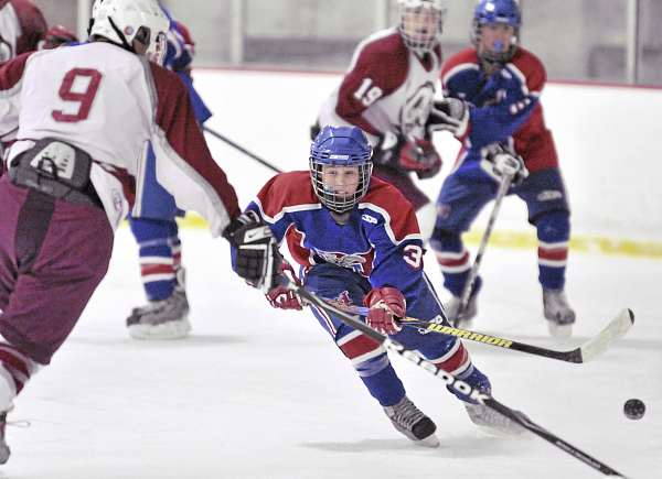 Bangor High School sophomore defensman Anthony Capuano (9) pokes the puck away from Messalonskee freshman left wing Joshua Towle (3) in the first period of Wednesday's hockey game at Sawyer Arena in Bangor. Bangor erupted for seven first-period goals en route to an 8-1 triumph.