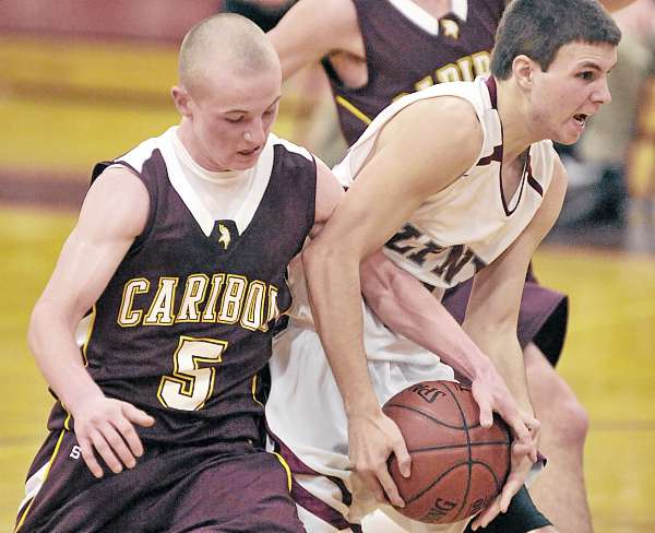 Mattanawcook Academy's Matt Voisine (15) gets some help dribbling the ball from Caribou's Chad Caverhill (5) as he goes to the basket in the first half of their game in Lincoln, Thursday night. (BDN Photo by Michael C. York)