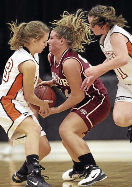 Brewer's Emily Mills, left, and Holly Nickerson struggle for possession with Bangor's Brianna McKenna, center, during their game at Brewer High School on Tuesday, December 21, 2010. Bangor defeated Brewer 48-30. (Photo by Jason P. Smith)