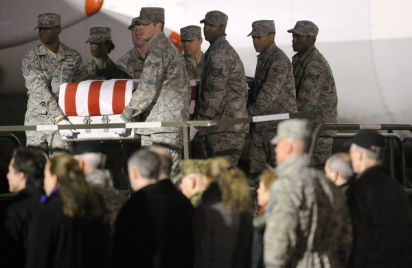 An Air Force carry team carries a transfer case containing the remains of Army Pvt. Buddy W. McLain Wednesday, Dec. 1, 2010 at Dover Air Force Base, Del. According to the Department of Defense, McClain, of Mexico, Maine, died while supporting Operation Enduring Freedom. (AP Photo/Steve Ruark)