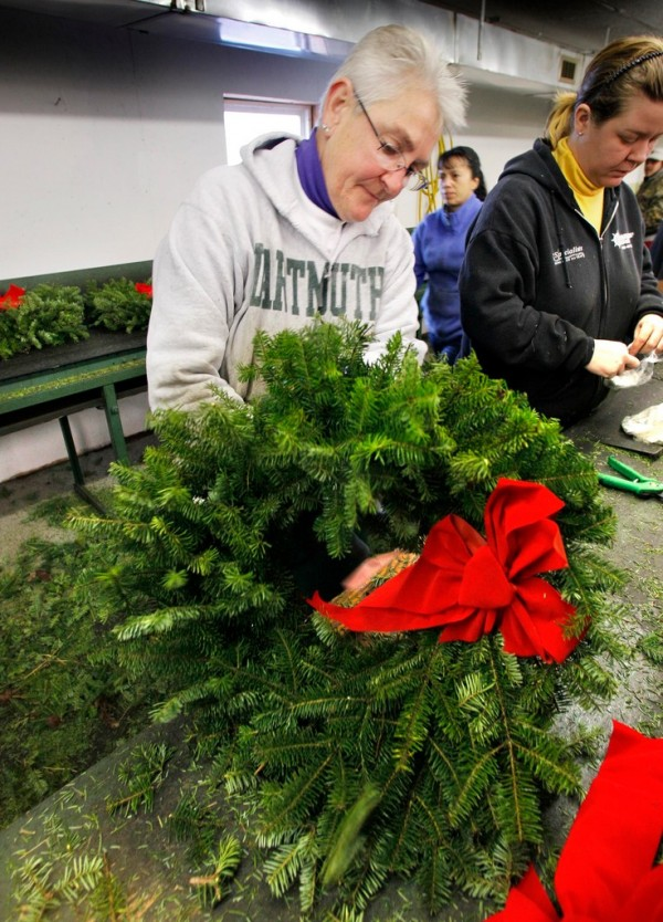 Deb Cameron adjusts a bow on one of 200,000 wreaths destined for a veteran's grave site, Friday, Dec. 3, 2010, at the Worcester Wreath shop in Harrington, Maine.  A convoy of tractor trailers on the Wreaths Across America mission will leave Harrington on Sunday, Dec. 5.  The mission, which started by laying wreaths at Arlington National Cemetery 19 years ago, now sends wreaths to all 50 states. (AP Photo/Robert F. Bukaty)(AP Photo/Robert F. Bukaty)