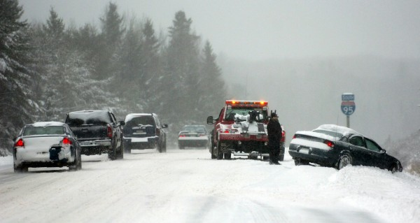 Traffic on Interstate 95 southbound creeps along as a wrecker prepares to remove a car that had slipped off the road on Monday, December 6, 2010. Numerous accidents along the I-95 corridor kept police and wrecker crews busy. (Bangor Daily News/Kevin Bennett)