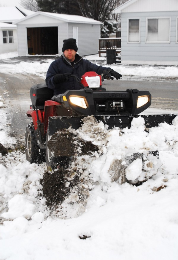 Scott Cyr of Madawaska plows snow using his 4-wheeler on 7th Ave. Snowfall had tapered off by mid-morning, but more was expected later. (Bangor Daily News/Matt Wickenheiser)