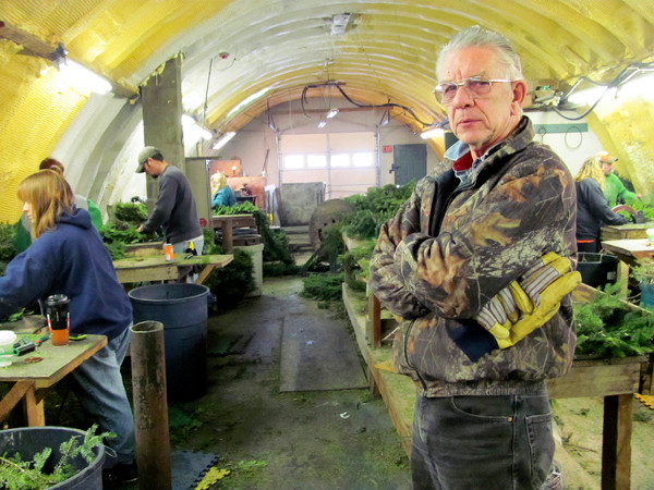 Ambrose &quotTom&quot McCarthy Jr. of Skowhegan, owner of Central Maine Wreath, poses on December, 7, 2010, while about a dozen workers around him create wreaths, crosses, candy canes and kissing balls out of balsam fir. McCarthy, who has been in the wreath business for 31 years, estimates he's sold more than 25,000 wreaths this year. He called that a respectable tally, but it's a fraction of the company's peak production in the early 1990s. (Bangor Daily News/Christopher Cousins)