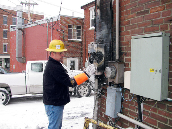 A Central Maine Power worker tries to fix a short-circuited electric meter box that caused a downtown Belfast block to be without power for part of the afternoon on Monday, Dec. 6, 2010. The malfunctioning meter sent sparks flying through the air for some time, according to Belfast Fire Chief Jim Richards. (Bangor Daily News/ Abigail Curtis)