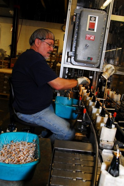 Bob Bourgoin inserts pumps into a line of perfume bottles at Evergreen Manufacturing in Madawaska. (Bangor Daily News/Matt Wickenheiser)