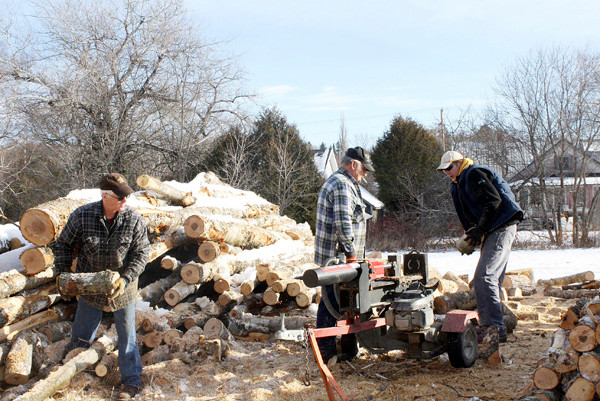 Ken Norton (left) helps move recently processed wood to a pile where it will season, while Eugene Wendell Stewart (center) and Justin Kobylarz use the wood splitter. The men volunteered their time to cut and split wood to help Aroostook County residents in need of fuel assistance. HOULTON PIONEER TIMES PHOTO BY ELNA SEABROOKS