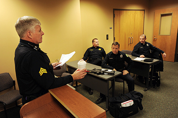 Sgt. Bob Bishop, left, leads a roll call for an evening shift of officers headed out on patrol at the Bangor Police Station on Wednesday, December 10, 2010.  Within the next three years, almost one-third of the force (28 of 83 officers) will be eligible for retirement.  Attending the roll call are officers Jeff Millard, second left,  Jim Dearing and John Robinson, right.  Bishop, a 26 -year veteran of the force, is already eligible for retirement and Millard, who started in 1986 is eligible in 2011. (Bangor Daily News/Kevin Bennett)