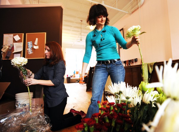 Kathryn Ravenscraft, left and Amber Small, right, owners of Sweetest Thing Event Design Studio in Bangor unpack fresh flowers at their Bangor studio for a local restaurant on Thursday, December 9, 2010. (Bangor Daily News/Kevin Bennett)