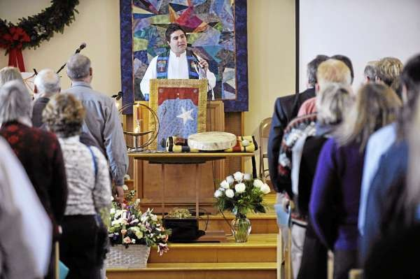 The Rev. Mark Glovin, center, addresses family and friends gathered at First Universalist Church in Rockland for a celebration of Katrina Windred's life. On Saturday the church was filled beyond capacity with family and friends who knew and loved Windred.(Bangor Daily News/John Clarke Russ)