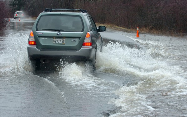 SURF'S UP-- These motorists, like others on the Meadow Road had to navigate a few submerged sections of roadway Monday, Dec. 13, 2010, after heavy rain continued to saturate Maine.  This area near the Patterson Road end had about 8 inches of water streaming across.  While the road was not closed, some drivers chose an alternative route.  Most still used the road, driving down the middle, some fast, some slow.  (Bangor Daily News/Scott Haskell)