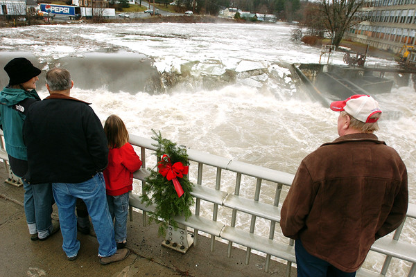 Pamela Schmidt, left, and her children, Hayden, obscured, and Ana, and friend Greg Dyer, second from left, along with Jeff Rowell, right, all of Dover-Foxcroft, stand along the West Main Street Bridge watching ice floes break up as high water curls over the Piscataquis River dam on Monday, December 13, 2010. (Bangor Daily News/Kevin Bennett)    CLICK-IT--VIDEO BY K. BENNETTOF WATER/ICE VOER THE DAM