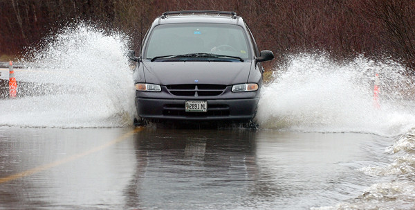 SURF'S UP-- Motorists on the Meadow Road in Hampden had to navigate a few submerged sections of roadway like this one near the Patterson Road end, which had about 8 inches of water streaming across Monday morning.  While the road was not closed, some drivers chose an alternative route around.  Many still used the road, driving down the middle, some fast, some slow, all leaving a large wake.(Bangor Daily News/Scott Haskell)