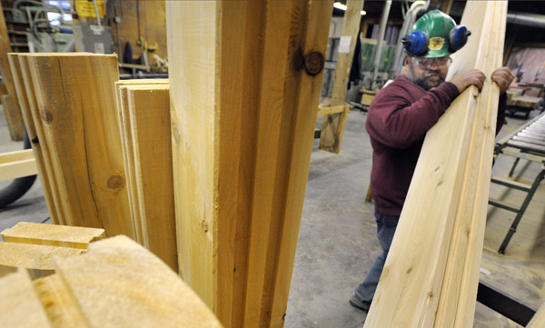Pete Gravelle stacks logs at the Moosehead Cedar Log Homes manufacturing facility in Greenville on Thursday. The company saw an influx of orders over the past couple of months for log home kits that are going to be delivered this fall and next spring. The logs are sorted and organized in the order they will be needed for the home to be assembled on the site. The company offers 60 plans ranging in sizes from about 400 square feet to 4,500 square feet.  (BANGOR DAILY NEWS PHOTO BY GABOR DEGRE)