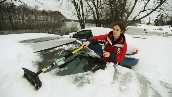 Moving her car to higher ground, UMaine student Ashley Kolofsky(cq) of Massachusetts brushes the snow off in the Steam Plant parking lot at the University of Maine on Wednesday, December 15, 2010 as the water from the Stillwater River encroaches the pavement. Students were alerted via email to move their cars.  A few were towed as a precaution. (Bangor Daily News/Kevin Bennett)