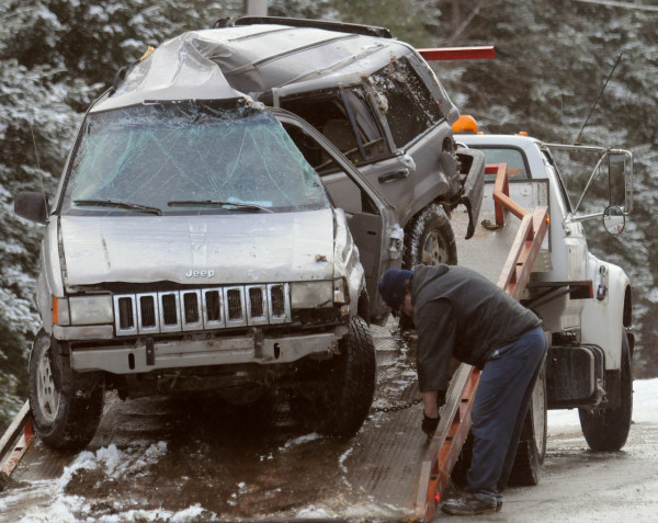 Tony Avila the owner of TA's Automotive secures a Jeep on his towtruck in Troy Wednesday.  One person was killed in the accident when the SUV went off the road and struck a utility pole about one mile West of the Baker Road on Route 9. (Bangor Daily News/Gabor Degre)