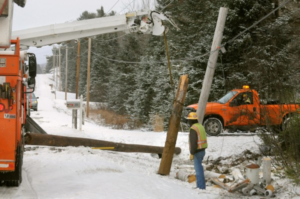 Central Maine Power eployees work on replacing the utility pole that was cliped by a vehicle that slid off Route 9 in Troy. (Bangor Daily News/Gabor Degre)