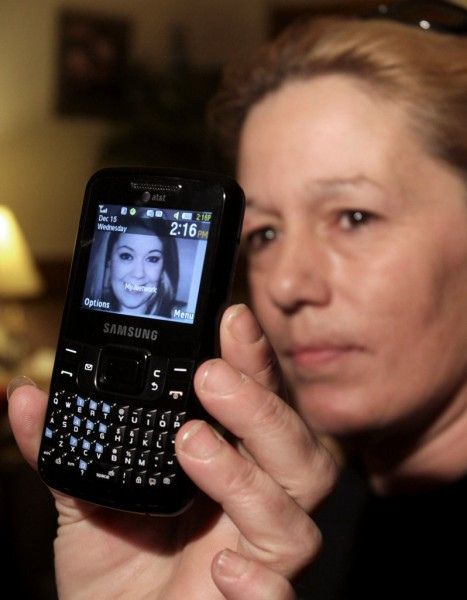 Lorraine Ela, of South Portland, Maine, displays her cell phone that has a picture of her missing daughter, while being interviewed by the media at her home on Wednesday, Dec. 15, 2010.  Ela's daughter, Megan Waterman, 22,  has been missing since June and authorities say they are trying to determine whether she is one four women's bodies found along a remote beach highway on New York's Long Island. (AP Photo/Pat Wellenbach)