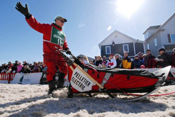 Long-time musher Don Hibbs of Millinocket, Maine waves to the crowd of thousands as his dog team carries him down Main Street in Fort Kent, Maine during the start of the Can-Am Crown 250 Saturday, March 6, 2010. Hibbs won the Can-Am Crown 250 in in 1997, 1999 and 2000 and has consistently done well at the event. (Bangor Daily News/John Clarke Russ)