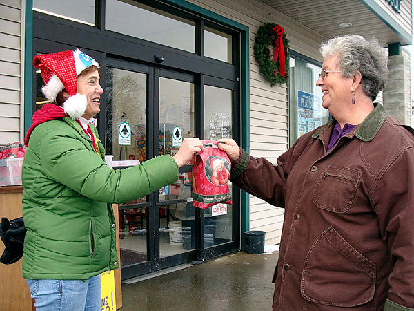 Rita Tibbetts of Guilford received a free gift Wednesday from Jenny Haskell of Sangerville. Haskell was passing out free toilet paper in a Christmas bag to customers leaving a Guilford grocery store. The toilet paper gift was an effort by Haskell to solicit more support for a contest she entered. (Bangor Daily News Photo by Diana Bowley)