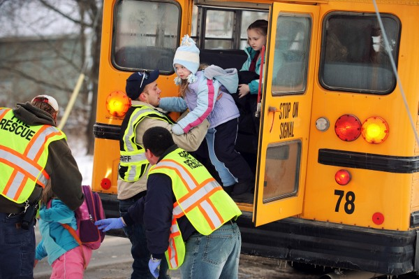 Orrington Fire and Rescue personnel help several of the 38 children from the Center Drive School in Orrington off the emergency exit of a school bus on Thursday, December 16, 2010 at the intersection of Center Drive and Route 15 after the school bus struck a van driven by Nanitalynn (cq) Hardy. Passengers in the van included Edward Hardy, John and Verona Stevens. (Bangor Daily News/Kevin Bennett)  WITH GAGNON STORY:  ORRBUSACCI