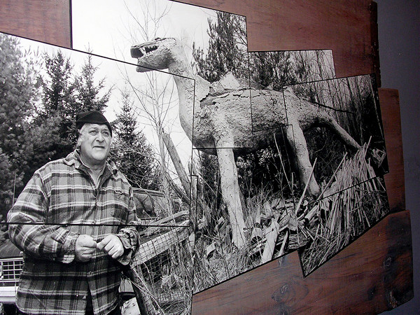 'THE DINOSAUR MAN'   Jerry Cardone, left, is pictured with one of his dinosaur sculptures in a photo taken by Portland photographer Tonee Harbert. Harbert's photographs of Cardone's work are on display at the Blue Moon Gallery in Houlton during &quot313 Military Street Reframed,&quot a show that will stay open until Aug. 2. Over the past 15 yars, Cardone- known to some as &quotThe Dinosaur Man&quot - has filled his 7-acre yard at 314 Military St. with carvings and pop culture constructions of dinosaurs, aliens, palm trees, totem poles and other pieces. (BANGOR DAILY NEWS PHOTO BY JEN LYNDS)