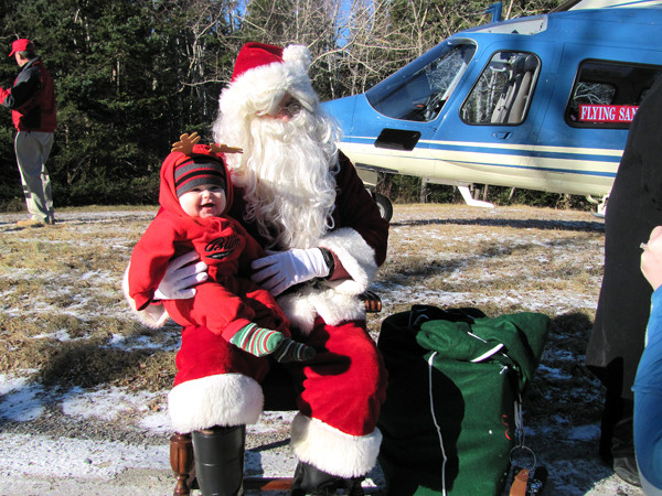 Eight-month-old Denver Nazworth sits on the Flying Santa's lap Saturday, December 18, 2010, at Owls Head Light State Park. Nazworth, wearing reindeer antlers, didn't seem to mind that Santa arrived in a helicopter instead of behind eight reindeer. (Bangor Daily News/Christopher Cousins)