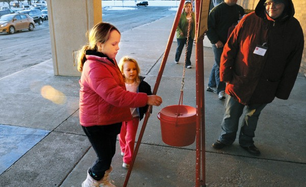 Zoe Vittum, 8, (left) and her sister Riley, 4, of Brewer walk up to the Salvation Army donation bucket to drop some money into it as they came to the Bangor Mall with their parents on Friday, Dec. 17, 2010.  Their mother, Denise Vittum, said that they try to give as much as in previous years.  &quotWe might cut corners somewhere else so we can give for the holidays.  We teach our kids that Christmas is not just about us,&quot she said.  Salvation Army bell ringer Melissa Bomar (right) said that people have been generous this season, but some might give less due to their own situation. (Bangor Daily News/Gabor Degre)
