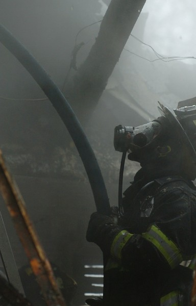 A Bangor firefighter feeds a hose to fellow firefighters from the second floor of a fire in a 5-unit apartment building located at 240 Center Street in Bangor on Monday, December 20, 2010. (Bangor Daily News/Kevin Bennett)
