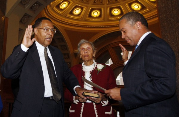Massachusetts Gov. Deval Patrick, right, reenacts the swearing in of Roderick L. Ireland, left, as Ireland's mother Helen Ireland holds the Bible, Monday, Dec. 20, 2010, in Boston. Ireland was sworn in as the first black chief justice of the Supreme Judicial Court. (AP Photo/Bizuayehu Tesfaye)