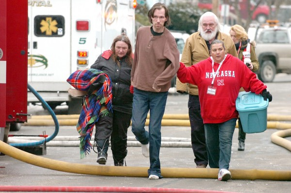 Two unidentified residents (left and second left) who escaped a fire in their 5-unit apartment house Monday morning , Dec. 20, 2010, on Center Street in Bangor are helped to a neighboring apartment by Red Cross worker Corina Hamlin, right, and her husband, Jef Hamlin (cq). (Bangor Daily News/Scott Haskell)