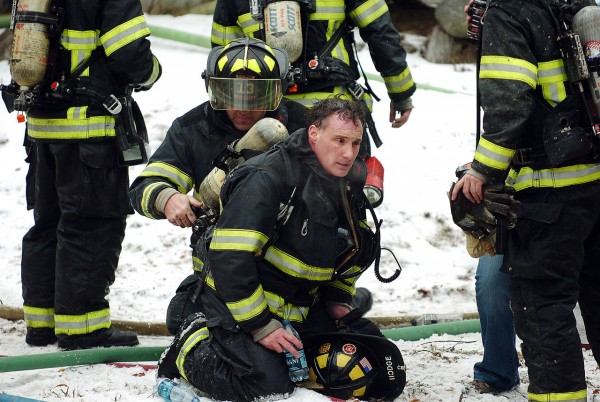 Bangor firefighter Greg Hodge, center, has his air tank changed by a fellow firefighter at the scene of a fire in a 5-unit apartment house at 240 Center Street in Bangor on December 20, 2010. (Bangor Daily News/Kevin Bennett)