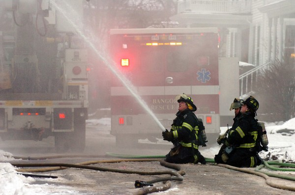 Bangor firefighters stationed on McKinley Street train a hose on the upper floor of a 5-unit apartment house at 240 Center Street, during a morning fire that caused major damage and displaced all the residents.  All the residents got safely out of their apartments.  (Bangor Daily News/Scott Haskell)