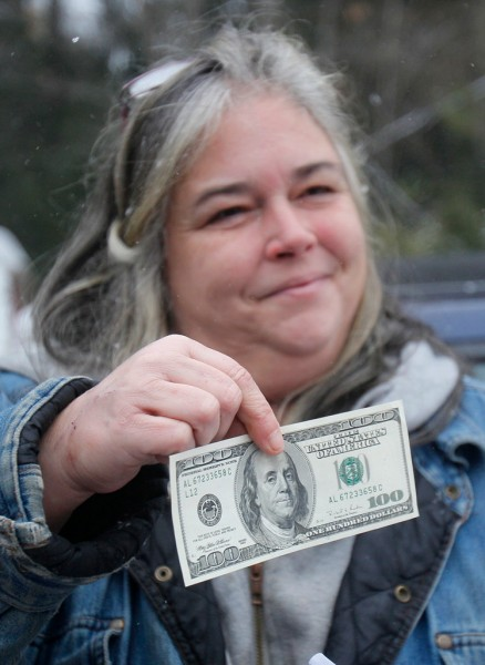Patricia Ange holds a $100 bill that she received from a secret Santa at a food pantry, Tuesday, Dec. 21, 2010, in Sebago, Maine.  A Portland, Maine, businessman in the red suit whose identity is kept secret, plans to hand out $20,000. (AP Photo/Robert F. Bukaty)