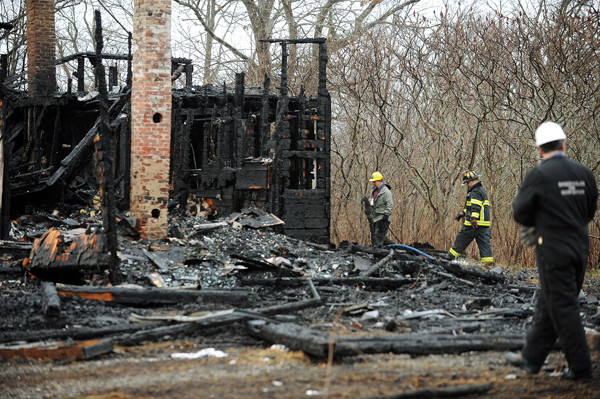 State Fire Marshal Ed Archer, left, Bangor firefighter Phil Hamm, center, and Bangor police Detective Cliff Worcester walk around the remains of a two-story home and attached barn at the end of Pushaw Road Extention in Bangor on Tuesday, December 21, 2010. Bangor firefighters responded at 7 p.m. on Monday, December 20, 2010 to reports of flames and found the abandoned structure engulfed in fire. (Bangor Daily News/Kevin Bennett)