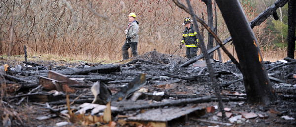 State Fire Marshal Ed Archer, left, and Bangor firefighter Phil Hamm walk around the remains of a two-story home and attached barn at the end of Pushaw Road Extention in Bangor on Tuesday, December 21, 2010.  When firefighters arrived on scene Monday night around 7 p.m., the abandoned buildings were engulfed in fire.(Bangor Daily News/Kevin Bennett)