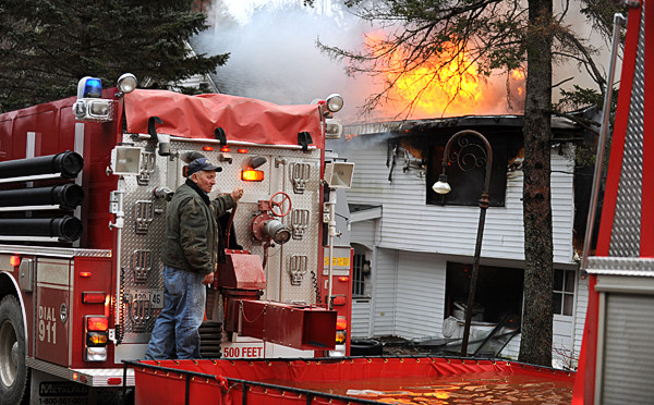 Tanker trucks formed a line to keep a portable tank filled with water at 14 Twining Road in Winterport on Tuesday, December 21, 2010. Kyle Stoops, property owner was playing with a new dog outside in a back yard when he noticed his house on fire. (Bangor Daily News/Kevin Bennett)